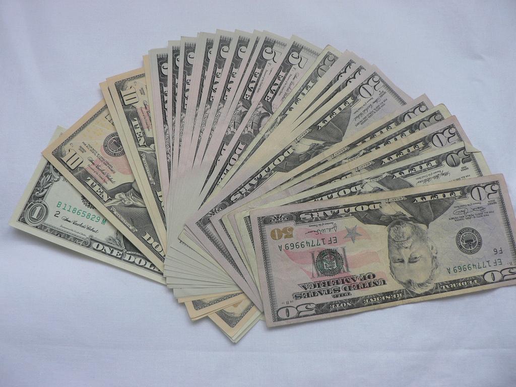 Фото пачки денег веером разложенную на столе (доллары)