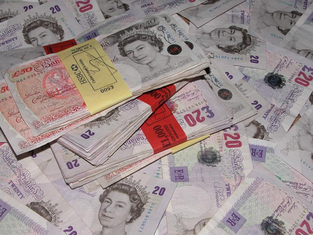 Фото разбросанной на столе пачки денег (английских фунтов)