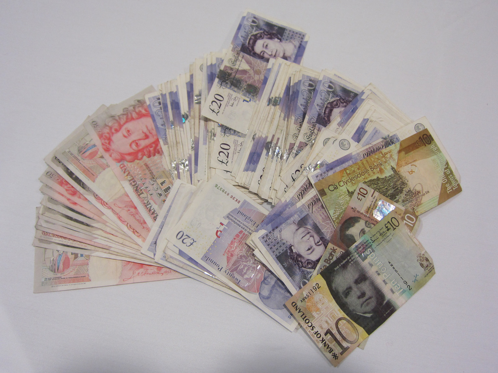 Фото пачки денег веером разбросанных на столе