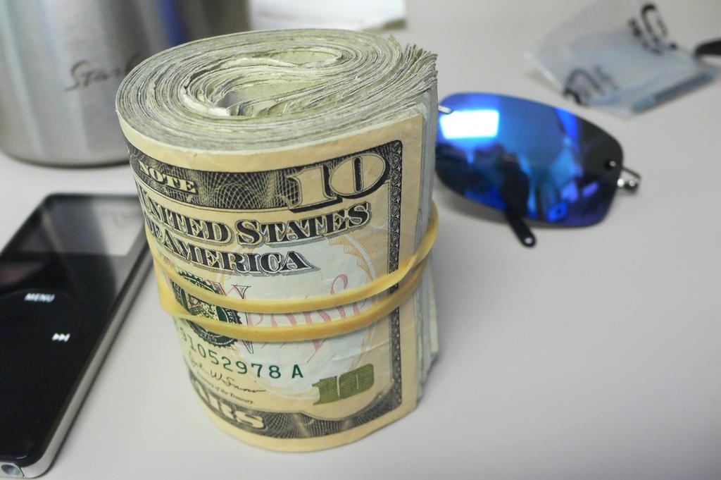 Фото свернутой цилиндром пачки денег (долларов)